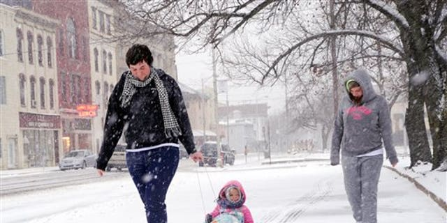 Marissa Birster, right, her little sister, Diamond Devalle, 3, and their friend Dylan Sessions walk along Indepedence Street in Shamokin on a snowy Saturday, Dec. 14, 2013. (AP Photo/The News-Item, Mike Staugaitis)