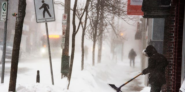 A man clears a sidewalk in blizzard conditions in Halifax, Nova Scotia, on Jan. 3, 2014.