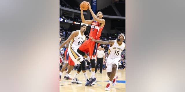 Washington Wizards' Otto Porter (22) , goes up to shoot while defended by New Orleans Pelicans' Alexis Ajinca (42) and John Salmons (15) during the second half of an NBA preseason basketball game in Jacksonville, Fla., Wednesday, Oct. 8, 2014. (AP Photo/Gary McCullough)