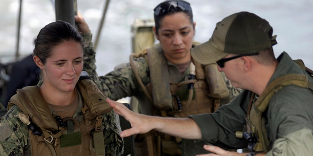 In this Aug. 13, 2013 file photo, U.S. Navy Master-at-Arms Third Class Danielle Hinchliff, left, and Master-at-Arms Third Class Anna Schnatzmeyer, center, participate in a U.S. Navy Riverine Crewman Course under instructor Boatswain's Mate Second Class Christopher Johnson, right, on a Riverine Assault Boat at Camp Lejeune, N.C. (AP Photo/Gerry Broome, File)