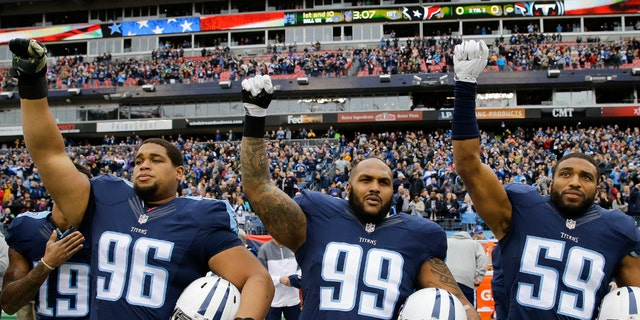 Tennessee Titans players Al Woods (96), Jurrell Casey (99), and Wesley Woodyard (59) raise their fists at the end of the national anthem before an NFL football game against the Houston Texans on Jan. 1, 2017, in Nashville, Tenn.