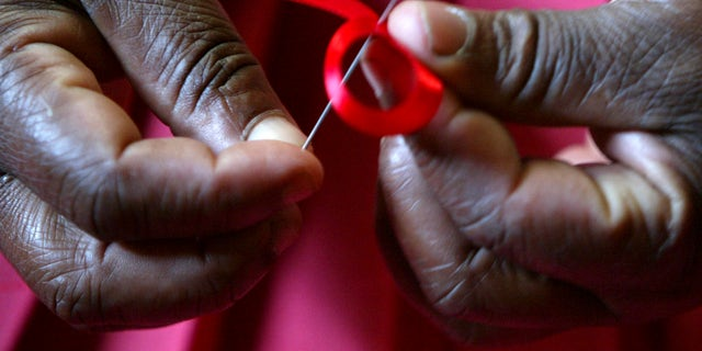 A Kenyan woman prepares ribbons ahead of December 1st, the World Aids Day at Beacon of Hope centre in Nairobi. (REUTERS/Antony Njuguna/Files)