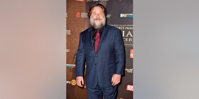 """Russell Crowe displays his portly frame and bushy beard as he attends the """"Gladiator in Concert"""" event with Connie Nielsen and Francesco Totti. June 6, 2018"""