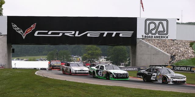 ELKHART LAKE, WI - JUNE 21: (L-R) Alex Tagliani, driver of the #22 Discount Tire Ford, Dakoda Armstrong, driver of the WinField Ford and Brian Scott, driver of the #2 Shore Lodge Chevrolet, move under a bridge during the Gardner Denver 200 Fired Up by Johnsonville race at Road America on June 21, 2014 in Elkhart Lake, Wisconsin. (Photo by Jonathan Daniel/Getty Images)