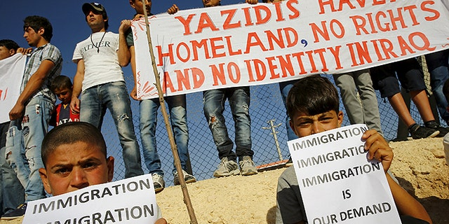 June 20, 2015: Yazidi refugees hold banners at a Syrian and Iraqi refugee camp in the southern Turkish town of Midyat. (REUTERS)