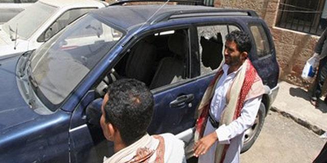 Mar. 18, 2012: Yemenis gather around a damaged vehicle purported to belong to an American teacher shot by gunmen in Taiz, Yemen.