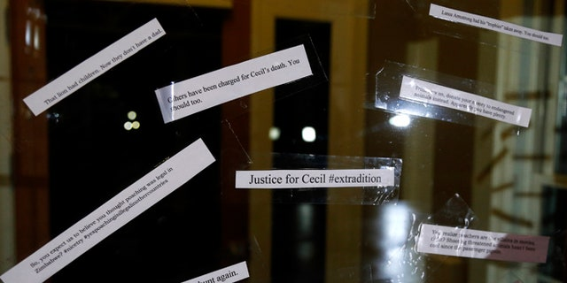 Small notes are placed on the front door of the dental practice of Walter Palmer.