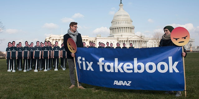 Avaaz campaigners hold a banner in front of 100 cardboard cutouts of the Facebook founder and CEO stand outside the U.S. Capitol, before Mark Zuckerberg testifies before the Senate, in Washington on Tuesday, April 10, 2018.