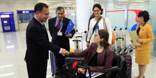FILE - In this May 2, 2017, file photo, Catalina Devandas Aguilar, U.N. Special Rapporteur on the Rights of Persons with Disabilities, shakes hands with Kim Mun Chol, left, chairman of the Central Committee of the Korean Federation for the Protection of the Disabled, at Pyongyang's international airport, in Pyongyang, North Korea. Devandas Aguilar is the first U.N. Human Rights Council (OHCHR) official to visit North Korea. (AP Photo/Jon Chol Jin, File)