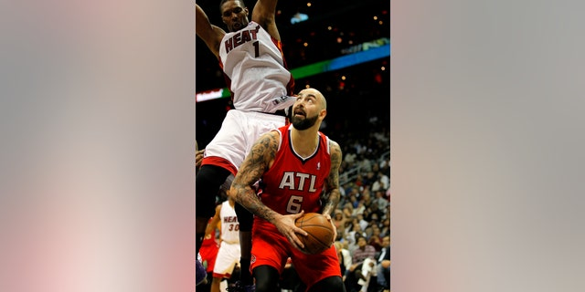 Atlanta Hawks center Pero Antic (6) looks to shoot as he is defended by Miami Heat center Chris Bosh (1) in the fourth period of an NBA basketball game in Atlanta, Monday, Jan. 20, 2014. The Hawks won 121-114. (AP Photo/Todd Kirkland)