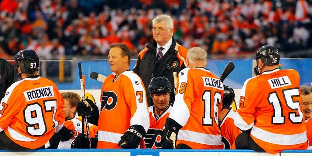 FILE - In this Dec. 31, 2011, file photo, members of the Philadelphia Flyers Alumni team gather on the bench in front of coach Pat Quinn, center, during the Winter Classic Alumni hockey game with the New York Rangers Alumni team in Philadelphia. Quinn, a former defenseman and longtime NHL coach and executive who brought a gruff and passionate presence to hockey across the decades, has died at 71. He died Sunday, Nov. 23, 2014, in Vancouver, British Columbia, after a long illness, the Hockey Hall of Fame and the Western Hockey League's Vancouver Giants said Monday. (AP Photo/Tom Mihalek, File)