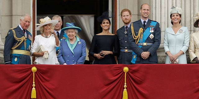 Members of the royal family gather on the balcony of Buckingham Palace, with from left, Prince Charles, Camilla the Duchess of Cornwall, Prince Andrew, Queen Elizabeth II, Meghan the Duchess of Sussex, Prince Harry, Prince William and Kate the Duchess of Cambridge, as they watch a flypast of Royal Air Force aircraft pass over Buckingham Palace.