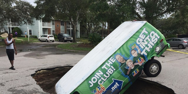 A boy photographs a van in a sinkhole in Winter Springs, Fla., Monday, Sept. 11, 2017, after Hurricane Irma. (Joe Burbank/Orlando Sentinel via AP)