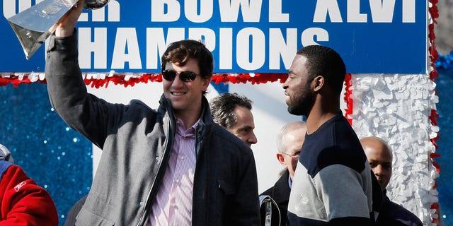 نيويورك ، نيويورك - 7 فبراير: قورتربك إيلي مانينغ # 10 (يسار) من فريق نيويورك جاينتس و Super Bowl XLVI MVP يحمل كأس فينس لومباردي كما ينظر جاستن تاك رقم 91 (على اليمين) من فريق نيويورك جاينتس خلال عمالقة وأمبير. # 39 ؛  موكب النصر في 7 فبراير 2012 في مدينة نيويورك.  هزم العمالقة نيو إنجلاند باتريوتس 21-17 في سوبر بول XLVI.  (تصوير أندرو بيرتون / جيتي إيماجيس)