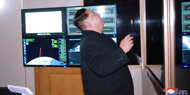 Kim Jong Un howls in laughter, though it is unclear if he is looking out at the rocket in the photograph.