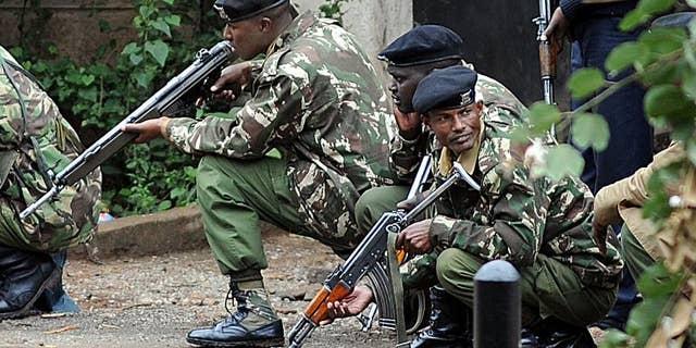 Armed Kenyan policemen take cover outside the Westgate mall in Nairobi on September 23, 2013.