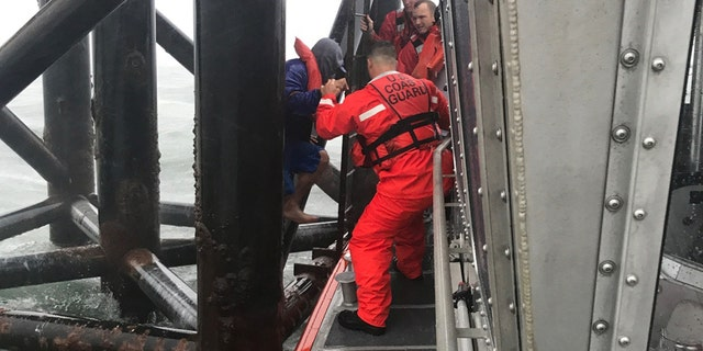 A 45-foot Response Boat-Medium boat crew from Station St. Petersburg, Florida, rescues two men clinging to a range light in Tampa Bay, Florida, Monday, July 31, 2017.