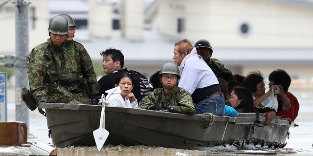 Japan Ground Self-Defense Force members use a boat to evacuate residents from a flooded area caused by heavy rains in Kurashiki, Okayama prefecture