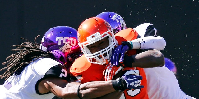 FILE - In this Oct. 19, 2013, file photo, Oklahoma State running back Rennie Childs (23) fights off a tackle by TCU cornerback Jason Verrett (2) and safety Chris Hackett (1) during the fourth quarter of an NCAA college football game in Stillwater, Okla. Childs provided Oklahoma State with a much-needed boost on the ground in last week's win over TCU. The running back could be counted on again this week when the Cowboys travel to Iowa State. (AP Photo/Sue Ogrocki, File)