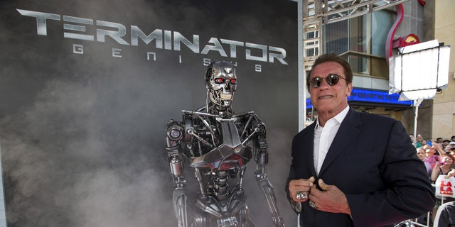 Cast member Arnold Schwarzenegger poses by a Terminator replica at the premiere of 'Terminator Genisys' in Hollywood, California June 28, 2015.