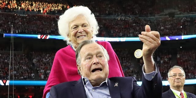 Barbara Bush stands behind her husband, former President George H.W. Bush, as he performs the ceremonial coin toss before Super Bowl 51 in Houston, Texas on Feb. 5, 2017.