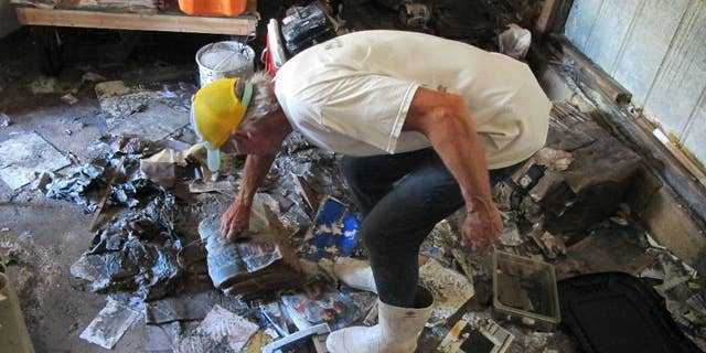 """In this Oct. 12, 2016 photo, Walter Coker surveys the damage in his furniture storage shed in Crescent Beach, Fla. Coker runs Genung's Fish Camp and Marina on the shore of the Matanzas River, and saw storm surge from Hurricane Matthew run """"like a river"""" through his property, tearing apart the storage shed and the tackle shop. He doesn't have flood insurance because he said it was too expensive, so is hoping to rebound with the help of neighbors and the community. (AP Photo/Jason H. Dearen)"""