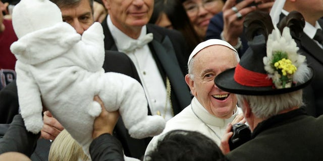 DEC. 7: Pope Francis smiles to a baby as he arrives to lead the general audience in Paul VI Hall at the Vatican