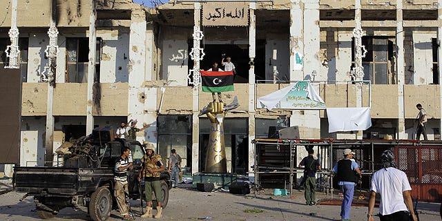 August 23: Rebel fighters seen inside the main Muammar Qaddafi compound in Bab al-Aziziya in Tripoli, Libya.