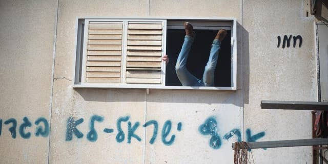"A settler jumps into a trailer in Amona outpost in the West Bank, Wednesday, Feb. 1, 2017. Israeli forces have begun evacuating a controversial settlement  Amona, which is the largest of about 100 unauthorized outposts erected in the West Bank without permission but generally tolerated by the Israeli government. The writing reads: ""Eretz Israel we did not  betray "". (AP Photo/Ariel Schalit)"