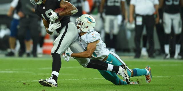 Oakland Raiders' Andre Holmes is tackled by Miami Dolphins' Brent Grimes during the NFL football game at Wembley Stadium in London, Sunday, Sept. 28, 2014. (AP Photo/Tim Ireland)