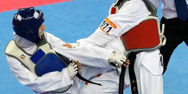 FILE - This is a Friday, Nov. 19, 2010 file photo of Raheleh Asemani of Iran, left, in action against  South Korea's Noh Eun-sil, during their women's under 62 Kg Taekwondo final at the 16th Asian Games in Guangzhou, China. The former-Iranian taekwondo fighter who was part of the Olympic team of refugee athletes has gained Belgian citizenship and wants to win a medal at the Rio de Janeiro for her new country, she said on Tuesday, April 26, 2016. (AP Photo/Eugene Hoshiko, File)