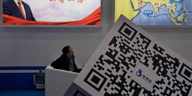 A conference attendee listens at a portrait of China's President Xi Jinping looms in the background, April 28, 2017.