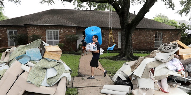 Michael Saghian carries a roll of bubble wrap and a box of sandwiches for workers helping remove items damaged by floodwaters from Tropical Storm Harvey from his home Wednesday, Aug. 30, 2017, in Houston