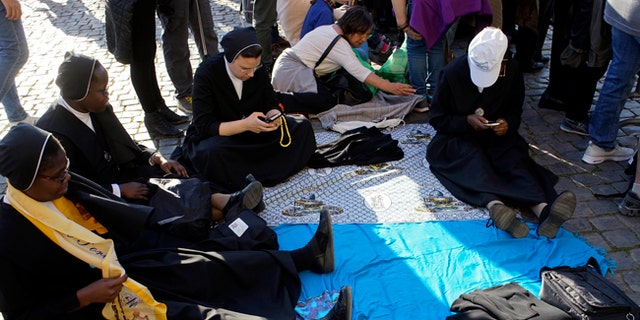 Nuns sit in the area around the ancient Colosseum a few hours ahead of the Way of the Cross procession, in Rome, Friday, April 14, 2017. Thousands of pilgrims are expected to flood the area surrounding the Colosseum to listen to the words of Pope Francis and watch the march leading to the cross. (AP Photo/Andrew Medichini)
