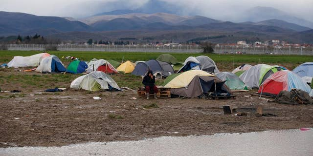 A migrant sits in front of his tent on a windy day in the makeshift refugee camp at the northern Greek border point of Idomeni, Greece, Thursday, March 24, 2016. Conditions in Idomeni, where thousands have been stranded since the border shut to refugees earlier this month, have steadily deteriorated, exacerbated by days of rain that have turned the fields into muddy swamps. (AP Photo/Darko Vojinovic)