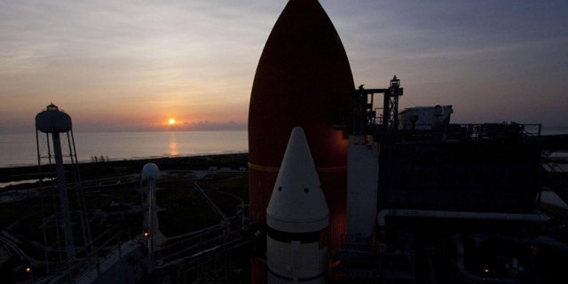 The sun rises over the Atlantic Ocean at NASA's Kennedy Space Center in Florida, illuminating space shuttle Atlantis' external fuel tank and solid rocket boosters on Launch Pad 39A. Launch is scheduled to take place for the STS-135 mission on July 8, 2011. This image was taken on June 23, 2011.