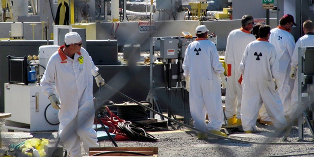 July 14, 2010: In this photo, workers at the Hanford nuclear reservation work around a a tank farm where highly radioactive waste is stored underground near Richland, Wash.