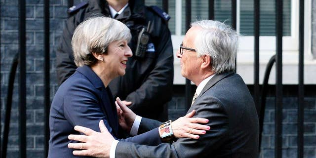 """FILE - In this April 4, 2017 file photo, Britain's Prime Minister Theresa May greets European Commission President Jean-Claude Juncker outside 10 Downing Street in London. Theresa May acknowledged Tuesday May 2, 2017 that Brexit """"will not be easy,"""" after EU officials accused Britain of underestimating the complexity of the task ahead. (John Stillwell/PA via AP)"""
