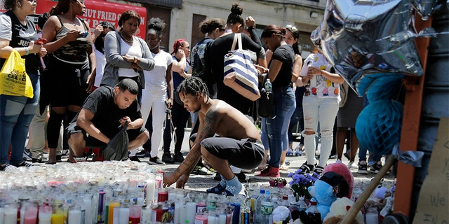People leave candles and other mementos at a memorial to Lesandro Guzman-Feliz near the site of his murder in the Bronx borough of New York.