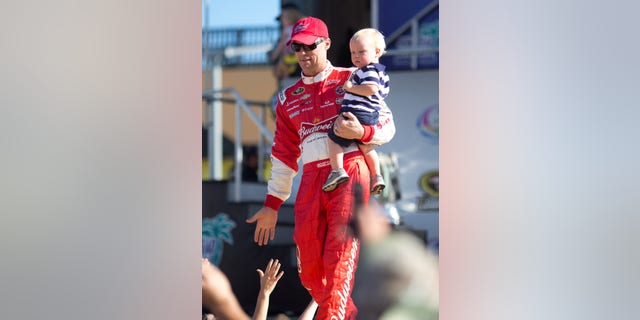 Kevin Harvick holds his with son, Keelan, as they greet fans during driver introductions before the NASCAR Sprint Cup Series auto race in Homestead, Fla., Sunday, Nov. 17, 2013. (AP Photo/J Pat Carter)