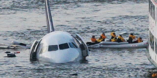 """FILE - In this Jan. 15, 2009 file photo, passengers in an inflatable raft move away from US Airways Flight 1549 that went down in the Hudson River in New York. Capt. Chesley """"Sully"""" Sullenberger III, First Officer Jeff Skiles and some passengers who were on the plane on Wednesday, Jan. 15, 2014 are expected to join some of the ferry crews who rescued them from the cold waters five years ago. (AP Photo/Bebeto Matthews, File)"""