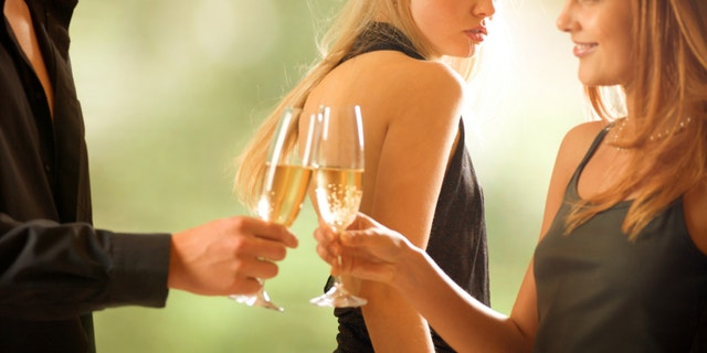 Young couple holding glasses with champagne and woman looking at them, outdoors, focus on woman with blond hair