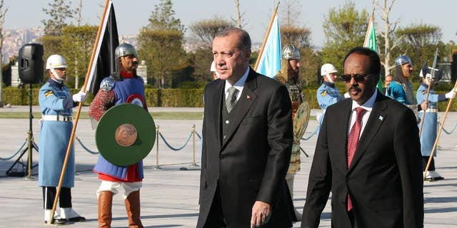 Turkey's President Recep Tayyip Erdogan, centre, walks with Somalia's President Mohamed Abdullahi Mohamed, also known as Farmajo, right, during a welcome ceremony at the Presidential palace in Ankara, Turkey, Wednesday, April, 26, 2017. Mohamed is in Turkey for an official visit. (Presidency Press Service via AP, Pool)