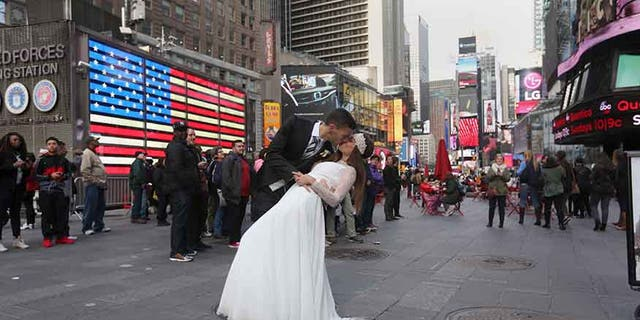 Berta and Jose Fernandez from Spain pose for wedding photos in Times Square in the Manhattan borough of New York November 11, 2015. REUTERS/Carlo Allegri  - RTS6K0E