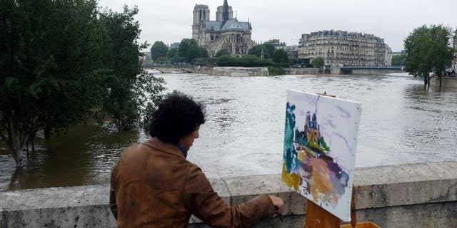 A man paints Notre Dame in Paris, in June 2016.