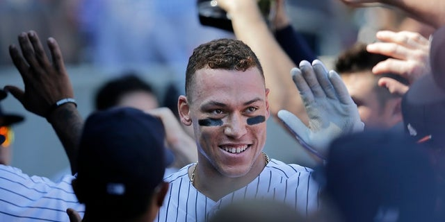 Yankees rookie Aaron Judge is greeted by his teammates in the dugout after hitting a two-run home run Monday.