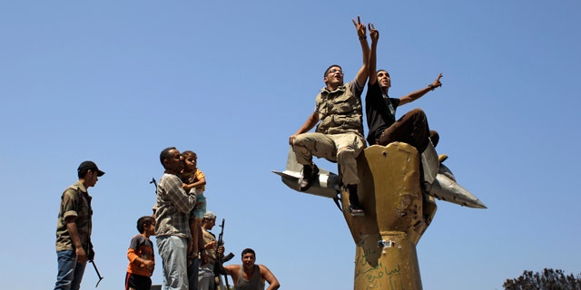 Aug.. 24: Rebel fighters celebrate as they stand on top of the monument inside Qaddafi's compound in Bab Al-Aziziya in Tripoli, Libya.