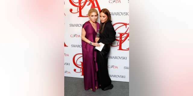 Ashley, left, and Mary-Kate smile backstage with their award for Womenswear Designer of the Year at the 2012 Council of Fashion Designers of America (CFDA) Fashion Awards in New York.