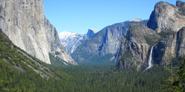 April 2013: Yosemite Valley as seen from Tunnel View with three of Yosemite National Park's best-known natural attractions: The El Capitan summit on the left, the granite peak known as Half Dome in the distant center, and Bridalveil Fall  on the right.