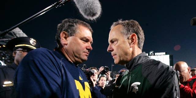 Michigan State coach Mark Dantonio, left, and Michigan coach Brady Hoke talk at midfield before an NCAA college football game, Saturday, Oct. 25, 2014, in East Lansing, Mich. (AP Photo/Al Goldis)